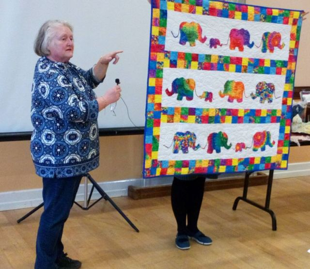 Tina Hawkes showing a baby quilt with rainbow elephants, appliqued with a narrow edge of Bondaweb